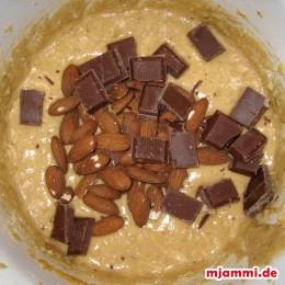 Schokolade und ganze Nüsse zu dem Teig geben.