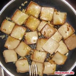 Das Öl in eine Pfanne geben und die Knoblauchzehen anrösten. Den Tofu rechts und links 2 min. anbraten.