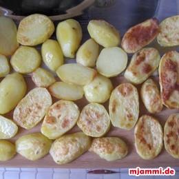 Wenn sie fertiggebacken sind, legt man erst die Kartoffeln in eine Auflaufform.