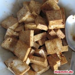 Tofu in Stücke schneiden. In heller Sojasauce marinieren.