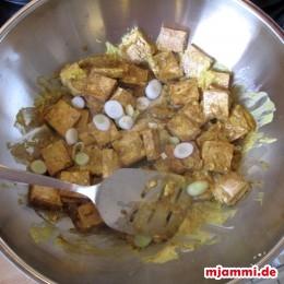 Den Tofu und die weißen Frühlingszwiebeln mit hinein geben und 1 Minute unter Rühren mitbraten. Restliche Kokosmilch und Kaffirlimettenblätter hineingeben und 3 Minuten kochen.