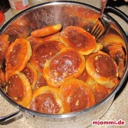 Sind die Roxakia fertig gebacken, dann legen wir sie in einen möglichst tiefes Blech oder flachen Topf und übergießen sie mit dem warmen Sirup. Dann decken wir die Roxakia zu damit sie den Sirup aufsaugen.