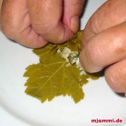 In die Innenseite legen wir 1-2 Teelöffel von der Reismischung und wickeln den Reis mit dem Weinblatt ein.