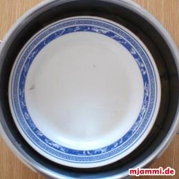 Die Dolmadakia mit einem Gefäß beschweren, beispielsweise einen Teller. Dann den Topf aufkochen lassen und anschließen auf kleiner Stufe weiter köcheln lassen, bis das ganze Wasser vom Reis aufgesaugt wurde.