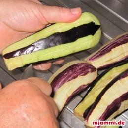 Zunächst schneiden wir den Strunk von den Auberginen ab, waschen sie und schaben an vier gleichmäßig verteilten Stellen die Haut in Streifen ab.