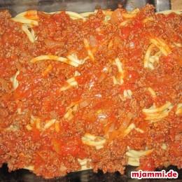 Για την σάλτσα σοτάρουμε το κρεμμύδι με λίγο ελαιόλαδο. Προσθέτουμε το κιμά και το τηγανίζουμε μέχρι που να διαλυθεί και να είναι καλοψημένος. Έπειτα ανακατεύουμε και τις τομάτες στο μείγμα με το κιμά και τα κρεμμύδια και αφήνουμε την σάλτσα να πάρει μια βράση. Αλατίζουμε την σάλτσα και καρυκεύουμε με πιπέρι και λιγάκι δυόσμο ή μαϊντανό. Απλώνουμε τα μακαρόνια στον πάτο ενός πυρέξ ή μιας γάστρας και μοιράζουμε από πάνω την σάλτσα με τον κιμά.