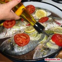 Das gleiche tun wir auch mit den Scheiben einer Fleischtomate. Reichlich Olivenöl auf die Doraden träufeln. Bei 200°C im Ofen für etwa 20 - 30 Minuten backen.