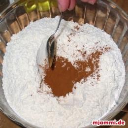 Βάζουμε σε μια λεκάνη το αλεύρι, ανοίγουμε μια λακούβα και προσθέτουμε τη ζάχαρη, λίγο αλάτι, την αλεσμένη κανέλα, το αλεσμένο γαρύφαλο, το μπεΐκιν πάουντερ και την τριμμένη φλούδα του πορτοκαλιού.