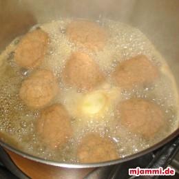Nun die gebackenen und kalt gewordenen Melomakarona aus dem Backblech in den Topf geben.
