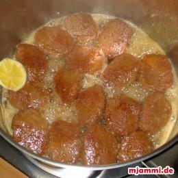 Die Melomakarona für etwa 5 Minuten den Sirup bei kleiner Flamme aufsaugen lassen und zwischendurch einmal wenden.