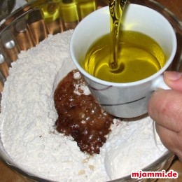 Ρίχνουμε το μείγμα με το χυμό πορτοκάλι και μισό φλιτζάνι κονιάκ στο σκεύος με το αλεύρι. Προσθέτουμε τρία φλιτζάνια ελαιόλαδο στο σκεύος ...