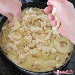 Από το αλεύρι το βούτυρο και την ζάχαρη φτιάχνουμε την ζύμη για την επίστρωση και την μοιράζουμε τρίβοντάς την πάνω από τα μήλα.