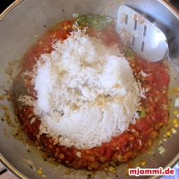 Die Tomaten dazugeben und so lange weiterbraten, bis die Flüssigkeit etwas andickt. Die Hitze runterdrehen und den Reis dazugeben.