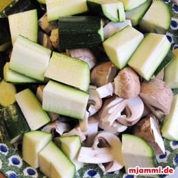 Die Zucchini vierteln und in ca. 3 cm lange Stückchen schneiden. Champignons vierteln. Auf eine große Schale legen, die noch in den Wok passt.