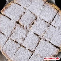 Wenn der Kuchen vollständig ausgekühlt ist, mit einem Messer die Zitronenriegel vom Rand lösen, in Riegel schneiden und mit Puderzucker bestreuen. Fertig! Guten Appetit!