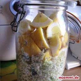 Zitronenviertel mit den Holunderblüten in ein Gefäß geben.