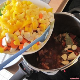 Εν το μεταξύ καθαρίζουμε τα λαχανικά και τα κόβουμε σε κύβους. Προσθέτουμε τα λαχανικά στο ζωμό και ανακατεύουμε. Καρυκεύουμε με μια πρέζα κύμινο και τους κόκκους πιπέρι.
