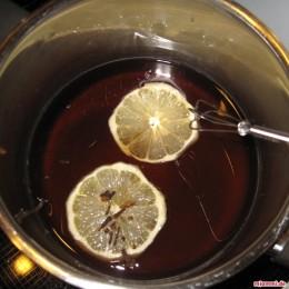 In einem kleinen Topf 1 1/2 Tasse Zucker in Wasser auflösen und die Zitronenscheiben sowie die Nelken dazu geben.