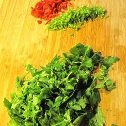 Petersilie waschen und dann die Blätter abzupfen. Dann die Chilie und die Petersilienstängel sehr klein schneiden.