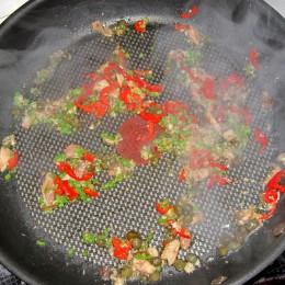 Βάζουμε το λάδι από την κονσέρβα με τον τόνο σε ένα τηγάνι και το ζεσταίνουμε. Ζουλάμε τις σκελίδες σκόρδου μέσα στο τηγάνι και προσθέτουμε το κάπαρη, τις σαρδέλες, τα κλωνάρια μαϊντανού και την κομμένη καυτερή πιπεριά.