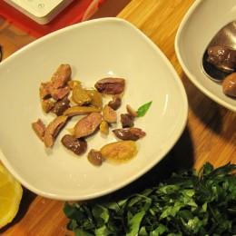 Oliven kleinschneiden. Petersilienblätter grob hacken.
