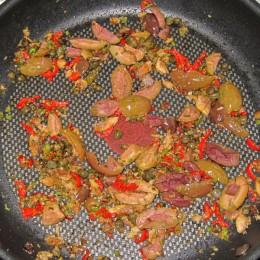 Έπειτα από 2 λεπτά προσθέτουμε τις ελιές και τα κάπαρη στο τηγάνι.