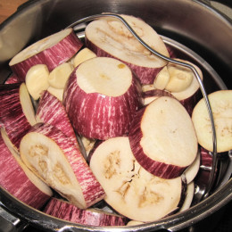 Einen Topf zu etwa einem Drittel mit Wasser füllen und einen metallenen Sieb zum Gemüsekochen in den Topf legen, so dass das Gemüse nur mit dem Dampf gegart wird. Hinein legen wir die Auberginen und die Knoblauchzehen, damit diese schön weich werden. Wir haben den Schnellkochtopf genommen und das Gemüse für knappe 20 min auf Stufe 2 kochen lassen.