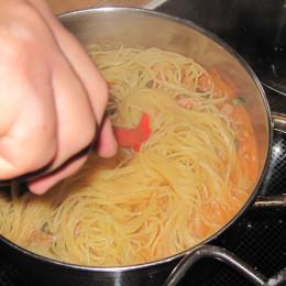 Die Spaghetti abtropfen lassen und mit der Sauce vermischen. Dabei Pfeffer, Salz, die Petersilie und das Olivenöl hinzugeben und umrühren.