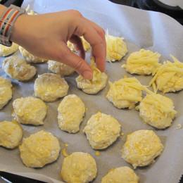 Das Ei aufschlagen. Den Teig mit dem Ei bestreichen und mit Käse bestreuen.