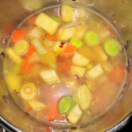 Προσθέτουμε ένα λίτρο νερό και καπακώνουμε την χύτρα. Αφήνουμε στη δεύτερη βαθμίδα να βράσουν για 10 λεπτά. Εν το μεταξύ κόβουμε τα λαχανικά για το ψητό μέρος σε μικρά κομμάτια. Μόλις τελειώσουν τα λαχανικά στην χύτρα, τα πολτοποιούμε με ένα μπλέντερ, τα αλατίζουμε και τα καρυκεύουμε με μαυροπίπερο και κουρκούμι. Αυτό που συνιστάτε είναι να μην γίνει πολύ σφιχτή σούπα. Έτσι αν χρειάζεται προσθέτουμε ακόμα λίγο νερό.