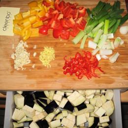 Auberginen und Paprika in 2 cm große Stücken schneiden. Frühlingszwiebeln in 3 cm lange Steifen schneiden. Knoblauch und Ingwer in ganz kleine Würfel teilen. Chilieschote in ganz kleine Scheiben schneiden.