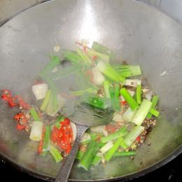 Προσθέτουμε μια κουταλιά της σούπας ελαιόλαδο στο βοκ και τηγανίζουμε τα φρέσκα κρεμμυδάκια, το σκόρδο, την πιπερόριζα και την καυτερή πιπεριά για περίπου ένα λεπτό.