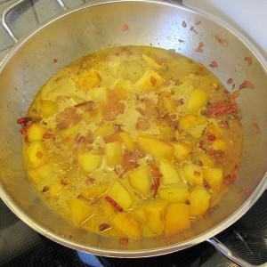 Έπειτα προσθέτουμε τις πατάτες και την σκόνη κάρυ και τηγανίζουμε για δύο λεπτά.  Σβήνουμε με νερό, γάλα ινδικής καρύδας και την σκόνη για ζωμό λαχανικών. Αφήνουμε το μείγμα να σιγοβράσει για 12-15 λεπτά με κλειστό καπάκι μέχρι να γίνουν η πατάτες.