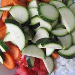 In der Zeit 2 Zwiebeln, 4 Knoblauchzehen, 1 Zucchini, 2 Möhren, 2 Tomaten kleinschneiden.