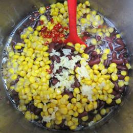 Dann die Dose Mais und die 2 Dosen Kidney-Bohnen, den Knoblauch und die Chilies dazugeben.