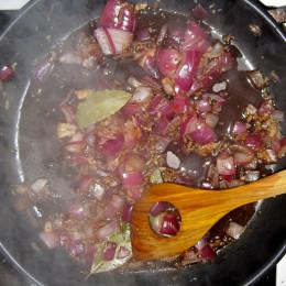 4 Lorbeerblätter in einem Topf anbraten. 4 Knoblauchzehen hineinpressen. Zwiebeln dazugeben. Wenn die Zwiebel glasig sind, etwas Balsamicoessig darunterrühren.