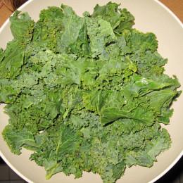 Grünkohl vom Stängel trennen, abwaschen und abtrocknen.