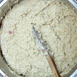 Den Reis unter Rühren mit jeweils einem Schöpflöffel Gemüsebrühe weiterkochen. (wie Risotto) Das dauert je nach Reis zwischen 20 und 40 Minuten. Dann 2 EL Tahini, die Zesten und den Saft von einer Zitrone, den EL Reisessig unterrühren.