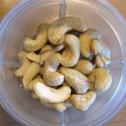 Cashews, Zesten und Saft einer halben Zitrone und 1/2 TL Salz in einen Mixer geben.